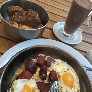 Turkish sausage with fried eggs and hot chocolate in a nearby cafe's garden.